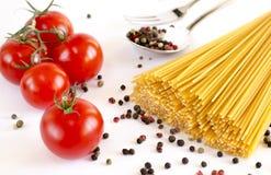 Spaghettis liegen auf einem weißen Hintergrund, zusammen mit Kirschtomaten, einem Löffel und einer Gabel lizenzfreie stockbilder