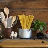 Spaghettis mit Bestandteilen für das Kochen von Teigwaren auf einem hölzernen Hintergrund, Draufsicht Konzept: Hausmannskost, Fet Lizenzfreie Stockfotografie