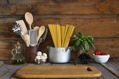 Spaghettis mit Bestandteilen für das Kochen von Teigwaren auf einem hölzernen Hintergrund, Draufsicht Konzept: Hausmannskost, Fet Stockbilder