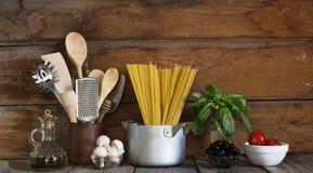 Spaghettis mit Bestandteilen für das Kochen von Teigwaren auf einem hölzernen Hintergrund, Draufsicht Konzept: Hausmannskost, Fet Lizenzfreie Stockfotos
