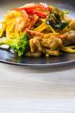 Spaghettis mit Garnelen- und SchweinefleischTomatensauce und Basilikum im schwarzen Teller auf weißem Holztisch stockfotografie