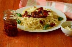Spaghettis mit Mozzarella, getrockneten Tomaten und Basilikum auf rotem Hintergrund Stockbild