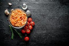 Spaghettis mit So?e von Bolognese in einer Glassch?ssel mit Tomaten, Rosmarin und Knoblauch lizenzfreie stockfotos