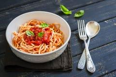 Spaghettis mit Tomatensauce und Basilikum in einer weißen Schüssel Lizenzfreie Stockfotos
