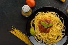 Spaghettis mit Tomatensauce und ihren Bestandteilen herum adjust Stockbilder