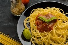 Spaghettis mit Tomatensauce und ihren Bestandteilen herum adjust Stockbild