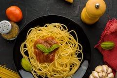 Spaghettis mit Tomatensauce und ihren Bestandteilen herum adjust Stockfoto