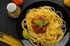 Spaghettis mit Tomatensauce und ihren Bestandteilen herum adjust Lizenzfreie Stockfotos