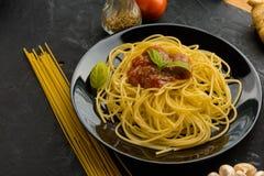 Spaghettis mit Tomatensauce und ihren Bestandteilen herum adjust Stockfotografie