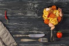 Spaghettis nisten mit Tomaten und Soße in einer Bratpfanne, hölzerner strukturierter Hintergrund Kirschtomaten, Serviette, Gabel, lizenzfreie stockbilder