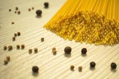 Spaghettis roh und Gewürze auf dem Tisch lizenzfreie stockfotos