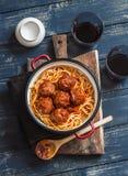 Spaghettis und Fleischklöschen in der Tomatensauce und in zwei Gläsern mit Rotwein auf hölzernem rustikalem Brett Stockbild