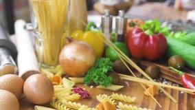 Spaghettis und Makkaroni mit Bestandteilen für das Kochen von Teigwaren auf Holztisch Frischgemüse und Eier für das Kochen des It stock video footage