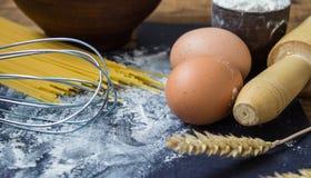 Spaghettis und Mehl und Eier auf schwarzem Hintergrund Lizenzfreies Stockbild