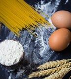Spaghettis und Mehl und Eier auf schwarzem Hintergrund Lizenzfreie Stockfotos