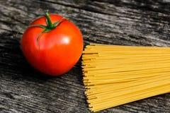 Spaghettis und Tomate auf einer rustikalen Holzbank stockfoto