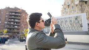 Spain - Barcelona, 12 August 2018: Man in leather jacket and black sun glasses taking photo of the gothic cathedral. Man in leather jacket and black sun glasses royalty free stock photos