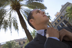Spain, Barcelona, businessman adjusting tie near palm tree in plaza, low angle view (tilt) Royalty Free Stock Photo