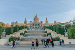 Spain - Barcelona. Tourists standing and walking around on the steps of the stairs of the National Museum of Art on Montjuic in Barcelona against a blue sky Royalty Free Stock Images