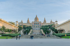 Spain - Barcelona. Tourists standing and walking around on the steps of the stairs of the National Museum of Art on Montjuic in Barcelona against a blue sky Royalty Free Stock Photos