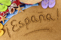 Spain Espana beach sand word writing. The word Espana (Spain) written on a sandy beach, with sombrero, starfish and flip flops Royalty Free Stock Images