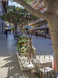 Spain, Canary islands, Tenerife, Puerto de la cruz, December 23, 2017: Street with tropical palm trees decorated with. Colourful baubles and gift box, ornaments royalty free stock images