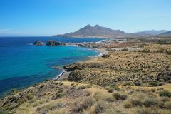 Spain coastal landscape Cabo de Gata natural park. Coastal landscape the village La Isleta del Moro with the massif of Los Frailes in background in the Cabo de royalty free stock images