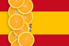 Spain flag and citrus fruit slices vertical row. Spain flag and vertical row of orange citrus fruit slices. Concept of growing as well as import and export of stock photos