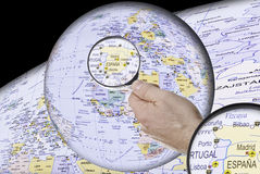 Spain on the globe. This image shows  Spain, under a magnifying glass, on a globe, on a black background with a map Royalty Free Stock Image