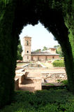 Spain. Granada. Alhambra. View of building with tower through arc of bush. Vertical view. Spain. Granada. Alhambra. View of building with tower through arc of Royalty Free Stock Photo