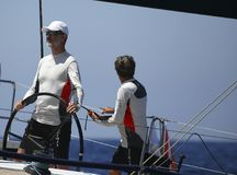 Spain king felipe steers aifos yacht during regatta. Spain King Felipe steers the Aifos sailing yacht during the kings cup sailing regatta in the island of royalty free stock photos