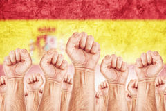 Spain Labour movement, workers union strike. Concept with male fists raised in the air fighting for their rights, Spanish national flag in out of focus Stock Images