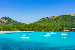 Spain Majorca beach bay of Cala Agulla in Cala Ratjada. Balearic Islands, Majorca beach of Cala Agulla, beautiful bay with tropical sea water and sailing boats Stock Photography
