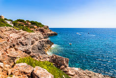 Spain Majorca cliff line scenery. Beautiful view of rocky cost scenery with boats at the coast, Mallorca island, Spain Mediterranean Sea, Balearic Islands Royalty Free Stock Photo