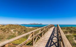 Spain Majorca island, boardwalk to beach and seaside of bay of Alcudia. Can Picafort, Platja de Muro, wooden footbridge over the sand dunes to the beach bay of Royalty Free Stock Photos