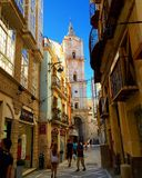 Spain. Malaga. Old town. Little lively street in the old part of the city. At the end of the street visible Church Stock Photos