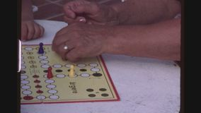 Ludo Or Pacheesi. SPAIN, MALLORCA, JULY 1983. Four Shot Sequence Of Grandparents Teaching Happy Little Girl A German Board Game Called Mensch Aergere Dich Nicht stock footage
