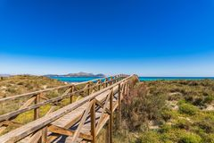 Spain Mallorca, sand dunes landscape at coast of by of Alcuida. Wooden footbridge over the sand dunes to the beach of Alcudia bay on Majorca, Spain Mediterranean Stock Photography