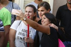 Spain Queen Letizia takes a selfie with villagers in the village of San Llorenc after floods killed many people vertical. Spain King Felipe and Queen Letizia royalty free stock photography