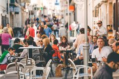 SPAIN, RONDA, 30 October 2016: People eating and drinking in a street cafe outdoors. People eating and drinking in a Spanish street cafe outdoors royalty free stock photo