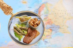 Spain tapas with map. Looking in on food of the world showing tapas of Spain with a magnifying glass or loop with European map in the background Royalty Free Stock Photography