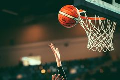 Female basketball player put the ball into the hoop to score points. stock photos