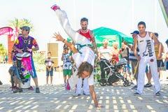 SPAIN-TORREVIEJA, ALICANTE, FELSEN GEGEN KREBS - 16. JUNI 2018: Gruppe der junge Leute-Trommel-Stoß-Frau demonstriert Capoeira lizenzfreie stockfotografie
