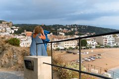 Spain, Tossa de Mar, August 2018. A girl examines the city through a telescope. A magnificent view of the beach with fishing boats from the fortress wall, the royalty free stock photography