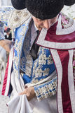 Spainish bullfighter putting itself the walk cape in the alley b Royalty Free Stock Image