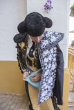 Spainish bullfighter putting itself the walk cape in the alley b Royalty Free Stock Images