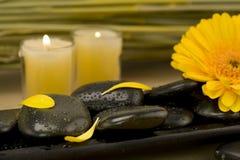Spainställning med pebbles och den gula blomman Arkivfoton
