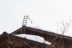 Spali l'attaccatura sulla scala con neve sul tetto Immagine Stock