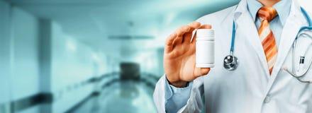Spalla del dottore With Stethoscope On che tiene una bottiglia delle pillole fra le sue dita Concetto medico dell'ospedale di san fotografia stock