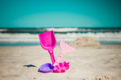 Spalla e giocattoli nella sabbia sulla spiaggia Immagini Stock